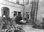 Puutarhan kukkaloistoa. Kuvassa ovat neidit Brusila (penkillä), Alma Koskinen (ovensuussa) ja Mandi Ekman (ikkunan luona).